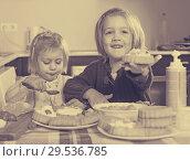 Купить «Two little girls with cream desserts», фото № 29536785, снято 14 декабря 2018 г. (c) Яков Филимонов / Фотобанк Лори