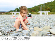 Cute happy smiling little girl building pebbles tower on the beach. Стоковое фото, фотограф ivolodina / Фотобанк Лори
