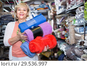 Купить «Adult female buyer choosing colour plaids in the textile store», фото № 29536997, снято 29 ноября 2017 г. (c) Яков Филимонов / Фотобанк Лори