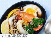 Купить «Spicy pan-Asian soup with squid, shrimp, egg noodles with sesame», фото № 29537237, снято 16 января 2019 г. (c) Яков Филимонов / Фотобанк Лори