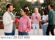 Купить «friends with drinks in party cups at rooftop», фото № 29537693, снято 2 сентября 2018 г. (c) Syda Productions / Фотобанк Лори