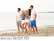 Купить «friends in striped clothes walking along beach», фото № 29537757, снято 13 июля 2014 г. (c) Syda Productions / Фотобанк Лори
