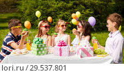 Купить «kids eating cupcakes on birthday party in summer», фото № 29537801, снято 27 мая 2018 г. (c) Syda Productions / Фотобанк Лори