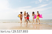 Купить «friends run with beach ball and swimming mattress», фото № 29537893, снято 29 июля 2018 г. (c) Syda Productions / Фотобанк Лори