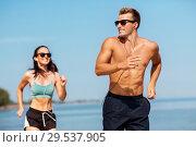 Купить «couple with earphones running along on beach», фото № 29537905, снято 1 августа 2018 г. (c) Syda Productions / Фотобанк Лори
