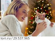 Купить «happy young woman with cat at home on christmas», фото № 29537965, снято 30 апреля 2016 г. (c) Syda Productions / Фотобанк Лори