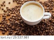 Купить «close up coffee cup and beans on wooden table», фото № 29537981, снято 7 апреля 2016 г. (c) Syda Productions / Фотобанк Лори
