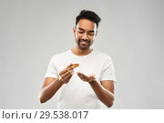 Купить «indian man applying grooming oil to his hand», фото № 29538017, снято 27 октября 2018 г. (c) Syda Productions / Фотобанк Лори