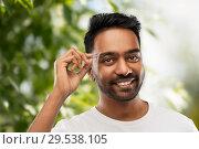 Купить «indian man with tweezers tweezing eyebrow hair», фото № 29538105, снято 27 октября 2018 г. (c) Syda Productions / Фотобанк Лори