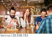 Купить «friends dining and drinking wine at restaurant», фото № 29538153, снято 8 ноября 2015 г. (c) Syda Productions / Фотобанк Лори
