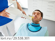 Купить «dentist making dental x-ray of patient teeth», фото № 29538301, снято 22 апреля 2018 г. (c) Syda Productions / Фотобанк Лори