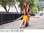 Купить «teenage girls riding skateboard on city street», фото № 29538305, снято 19 июля 2018 г. (c) Syda Productions / Фотобанк Лори