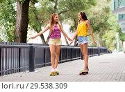 Купить «teenage girls riding skateboards in city», фото № 29538309, снято 19 июля 2018 г. (c) Syda Productions / Фотобанк Лори