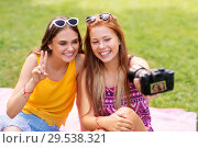 Купить «teenage bloggers recording video by camera in park», фото № 29538321, снято 19 июля 2018 г. (c) Syda Productions / Фотобанк Лори
