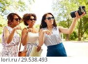 Купить «women with map travelling and recording video blog», фото № 29538493, снято 22 июля 2018 г. (c) Syda Productions / Фотобанк Лори