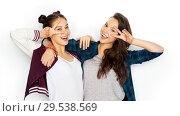 Купить «happy teenage girls hugging and showing peace sign», фото № 29538569, снято 19 декабря 2015 г. (c) Syda Productions / Фотобанк Лори