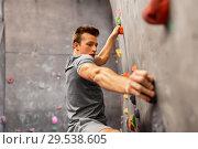 Купить «young man exercising at indoor climbing gym», фото № 29538605, снято 2 марта 2017 г. (c) Syda Productions / Фотобанк Лори