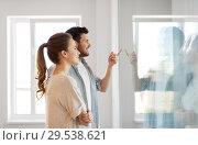 Купить «happy couple looking through window at new home», фото № 29538621, снято 4 июня 2017 г. (c) Syda Productions / Фотобанк Лори