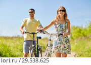 happy couple with bicycles on country road. Стоковое фото, фотограф Syda Productions / Фотобанк Лори