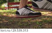 Купить «close-up shot of man's foot in sneakers walkining on the slackline and then jumps down from it. 4K slow mo footage», видеоролик № 29539313, снято 27 ноября 2018 г. (c) Uladzimir Sitkouski / Фотобанк Лори