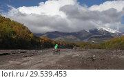 Купить «Quadracycle driving on mount road on dry river in direction of volcano», видеоролик № 29539453, снято 2 августа 2018 г. (c) А. А. Пирагис / Фотобанк Лори
