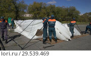 Купить «Group of rescuers setting up an army field tent, deploy campground on windy day», видеоролик № 29539469, снято 2 октября 2018 г. (c) А. А. Пирагис / Фотобанк Лори