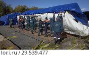 Купить «Group of rescuers setting up an army field tent, deploy campground on windy day», видеоролик № 29539477, снято 23 ноября 2018 г. (c) А. А. Пирагис / Фотобанк Лори