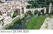 Купить «Aerial view of historic centre of Besalu with Romanesque bridge over Fluvia river, Catalonia, Spain», видеоролик № 29541833, снято 11 июня 2018 г. (c) Яков Филимонов / Фотобанк Лори
