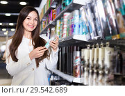 Smiling young female choosing haircare spray and other products at the shop. Стоковое фото, фотограф Яков Филимонов / Фотобанк Лори