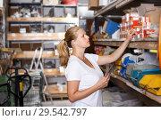 Купить «Woman with shop list and looking tools at shelves in build shop», фото № 29542797, снято 20 сентября 2018 г. (c) Яков Филимонов / Фотобанк Лори