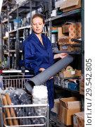 Купить «Young woman in uniform looking construction materials with basket in build shop», фото № 29542805, снято 20 сентября 2018 г. (c) Яков Филимонов / Фотобанк Лори