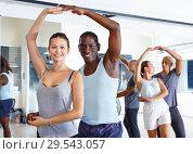 Young smiling people practicing passionate samba in dance class. Стоковое фото, фотограф Яков Филимонов / Фотобанк Лори