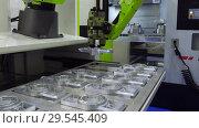 Купить «The robot arm sets the parts for machining in the CNC milling center», видеоролик № 29545409, снято 26 октября 2018 г. (c) Андрей Радченко / Фотобанк Лори