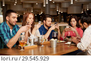 Купить «friends with smartphones at restaurant», фото № 29545929, снято 8 ноября 2015 г. (c) Syda Productions / Фотобанк Лори