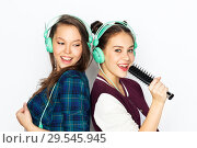 Купить «teenage girls in earphones listening to music», фото № 29545945, снято 19 декабря 2015 г. (c) Syda Productions / Фотобанк Лори