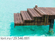 wooden pier with stair in sea water. Стоковое фото, фотограф Syda Productions / Фотобанк Лори