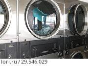 Купить «washing machines with clothes inside at laundromat», фото № 29546029, снято 28 февраля 2018 г. (c) Syda Productions / Фотобанк Лори