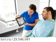 Купить «dentist showing panoramic dental x-ray to patient», фото № 29546041, снято 22 апреля 2018 г. (c) Syda Productions / Фотобанк Лори
