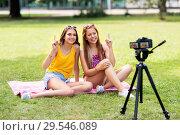Купить «teenage bloggers recording video by camera in park», фото № 29546089, снято 19 июля 2018 г. (c) Syda Productions / Фотобанк Лори