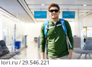 Купить «smiling man with backpack over airport terminal», фото № 29546221, снято 27 мая 2016 г. (c) Syda Productions / Фотобанк Лори