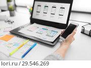 Купить «web designer with smartphone and laptop at office», фото № 29546269, снято 17 января 2018 г. (c) Syda Productions / Фотобанк Лори