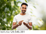 Купить «indian man applying grooming oil to his hand», фото № 29546381, снято 27 октября 2018 г. (c) Syda Productions / Фотобанк Лори