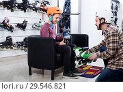 Купить «father assisting son in trying on roller-skates in sports store», фото № 29546821, снято 21 декабря 2016 г. (c) Яков Филимонов / Фотобанк Лори