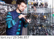 Купить «Male choosing baitcasting reel for rod for fishing in the sports shop», фото № 29546857, снято 16 января 2018 г. (c) Яков Филимонов / Фотобанк Лори