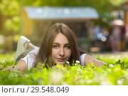 Купить «Charming Student Girl Sitting on Green Grass», фото № 29548049, снято 16 июля 2017 г. (c) Pavel Biryukov / Фотобанк Лори