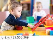 Купить «Cute little boy playing with abacus in nursery. Preschooler having fun with educational toy in daycare or kindergarten. Smart child learning to count.», фото № 29553369, снято 14 декабря 2018 г. (c) Оксана Кузьмина / Фотобанк Лори