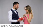Купить «happy man giving present in gift box to woman», видеоролик № 29553481, снято 6 декабря 2018 г. (c) Syda Productions / Фотобанк Лори