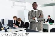 Купить «African American businessman standing at office on background with working colleagues», фото № 29553781, снято 24 марта 2018 г. (c) Яков Филимонов / Фотобанк Лори