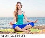 Купить «Young woman in blue T-shirt is sitting and practicing asana», фото № 29554053, снято 4 августа 2017 г. (c) Яков Филимонов / Фотобанк Лори