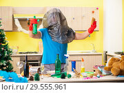 Купить «Young man cleaning kitchen after Christmas party», фото № 29555961, снято 27 июля 2018 г. (c) Elnur / Фотобанк Лори